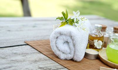 White towel with green spa setting on bamboo mat and wooden table