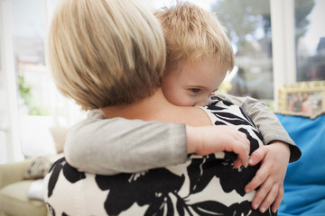 Young Boy Giving Mother Hug At Home