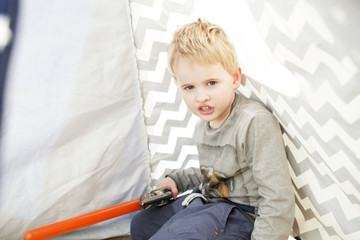 Boy Playing With Toy Sword Inside Tent At Home