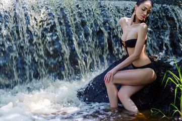 elegant woman in black swimsuit on background waterfall