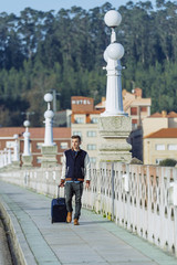 Man walking with a suitcase on a bridge