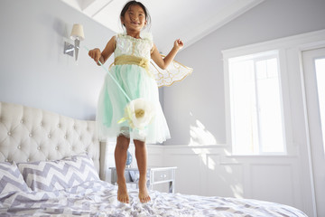 Girl Dressed In Fairy Costume Jumping On Bed At Home