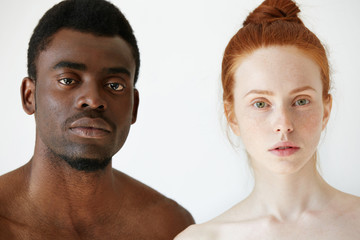 Love against racism. Black and white. Coffee and milk. Headshot of young loving multi-ethnic couple standing shirtless against white studio wall, looking at the camera. African man and Caucasian woman