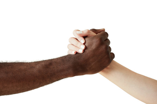 Arm wrestling against racism. Black and white human holding hands in a handshake, showing friendship and respect to each other. Close up shot of African man extending a helping hand to Caucasian woman