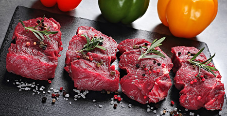 Steak. beef steak. Raw slices of sirloin beef steak with vegetable,spices,fresh herbs with rosemary chilli,and other ingredients,concrete background. Slate board.