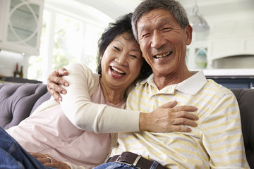 Senior Asian Couple At Home Relaxing On Sofa Together