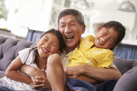 Grandfather And Granddaughters Relaxing On Sofa At Home