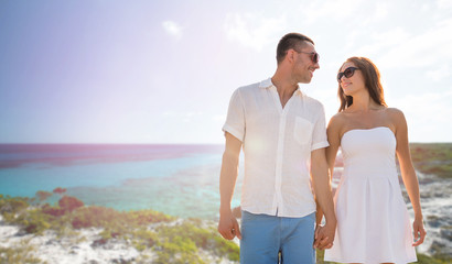 happy smiling couple over summer beach and sea