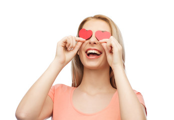 happy young woman with red heart shapes on eyes