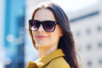 smiling young woman with sunglasses in city