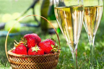 Strawberries in basket and champagne in glasses, tennis rackets and balls in background