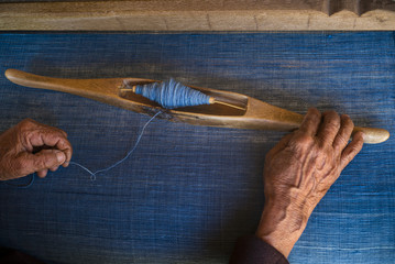 A woman weaving textiles dyed with indigo
