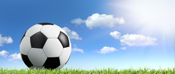 Fußball im Gras vor blauem Himmel mit Sonne und Wolken