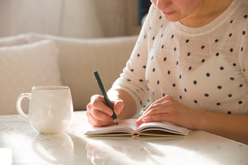 Woman sitting at the table, writing in the notebook and drinking coffee in nice light home interior. Working at home. Freelancer. writing down ideas. indoors.