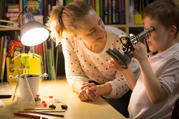 Young mother and elementary school kid boy looking into microscope at home. Family studying samples under the microscope. Science activities with children. Preparing for science lesson.