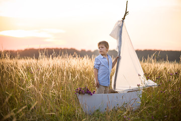 Boy seaman floats on a sailing boat in the field at sunset on a warm evening summer. Dreams of travel! Child floats on a handmade boat against the backdrop of a sunset.