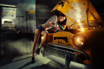Woman mechanic in sexy shirts is repairing an old car with the s