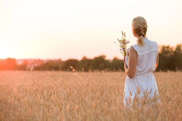 Back view on blond woman with flowers walking on the wheat field on sunset. Beautiful happy girl enjoying summer sun on the meadow. Lifestyle and summer concept. Outdoors.