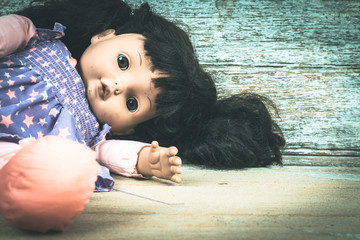 Concept Abandoned Person,Abandoned doll laying on old wooden ,vi