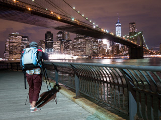 Person taking picture from Brooklyn Bridge with WTC at Night