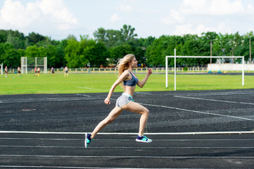 The sportswoman runs on a path at stadium.