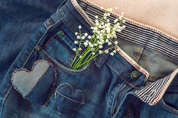 Bouquet of lily of the valley in  jeans pocket.