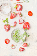 Flat lay of summer Strawberries  , bowl with mint and sugar on light vintage background, top view