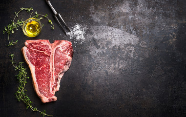 Raw T-bone Steak with fresh herbs and oil on dark rust metal background, top view, place for text, horizontal