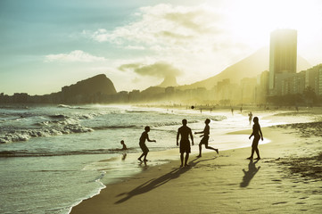 Beach football altinho silhouettes playing on the shore of Copacabana Beach at sunset in Rio de Janeiro, Brazil