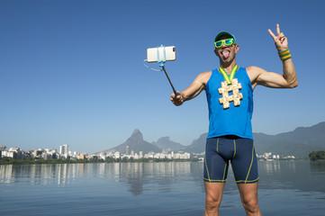 Hashtag gold medal athlete posing for a picture with his mobile phone on a selfie stick at Lagoa Rodrigo de Freitas Lagoon in Rio de Janeiro, Brazil