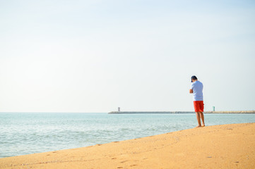 Man standing with the ocean in the background.