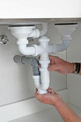 Plumber installing drain pipes under kitchen sink