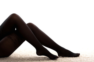 elegant female legs in dark tights crossed lying