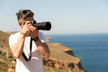 man taking a picture of the landscape against the sea