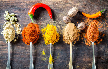 Tasty spices and herbs on old spoons