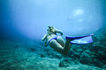 A woman floats in the ocean with fins in the background of pitfalls. Rear view under water