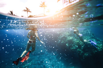 Two girls with nice butts floating in the ocean near the coral. Photo underwater