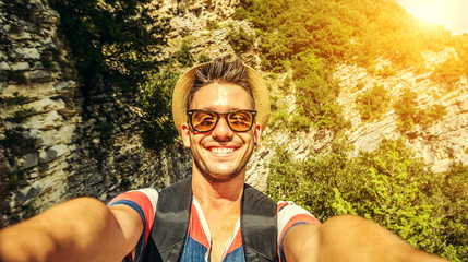 Handsome adventurous man taking selfie at mountain