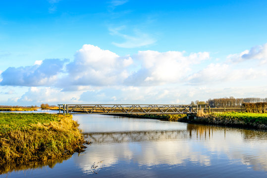 Foodbridge over a wide creek reflected