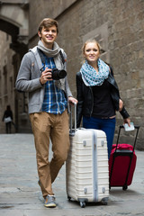Two travellers with digital camera walking through city street