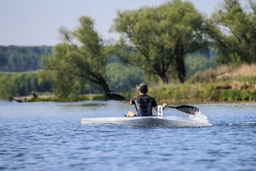young athlete on rowing kayak on lake during competition