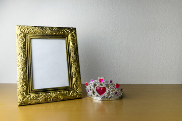 photo frame and crown on wooden table