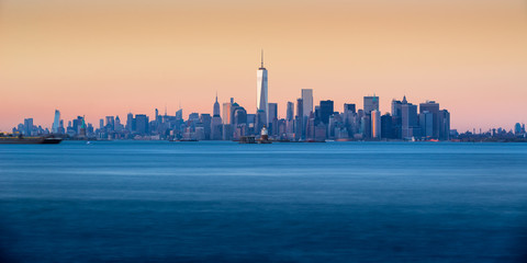 Fotomurales - Panoramic Sunset of Lower Manhattan and New York City Harbor with Financial District skyscraper