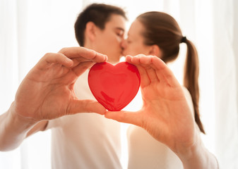 Young couple holding a heart while kissing.
