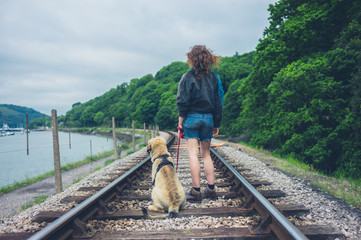 Young woman with dog on railroad tracks