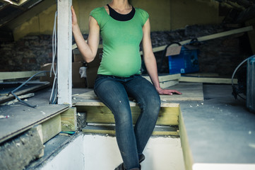 Pregnant woman sitting in attic