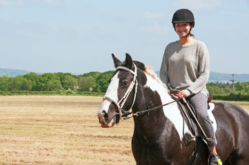 Young rider on her horse in a recently cut crop field