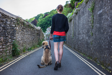 Woman walking puppy in small village