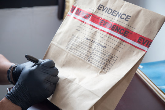 hand in glove writing on evidence bag and seal by red tape