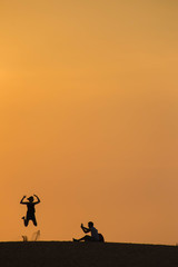 The couple is taking photo on red sand dune against sunset